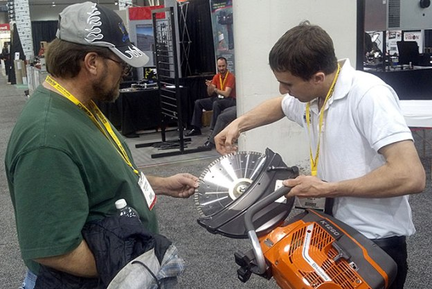 Gionni Mione of Desert Diamond Industries Showing Blade on Husqvarna Saw to Customer at World of Concrete 2013