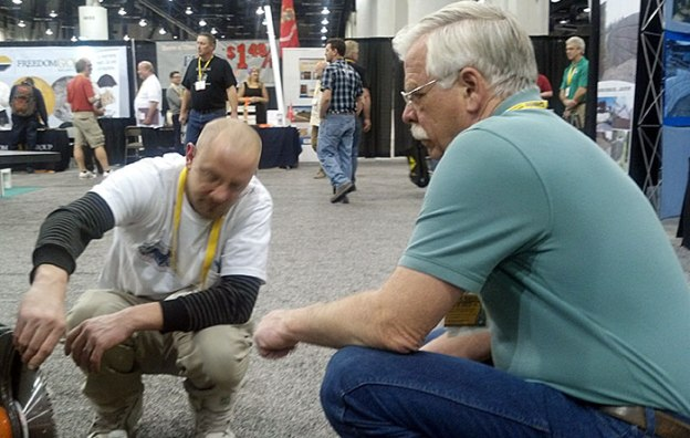 Glen Hellebrand of Desert Diamond Industries Crouching with Customer at World of Concrete