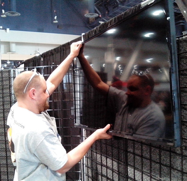 Glen Hellebrand Hanging a TV in Desert Diamond Industries' Booth at World of Concrete 2014